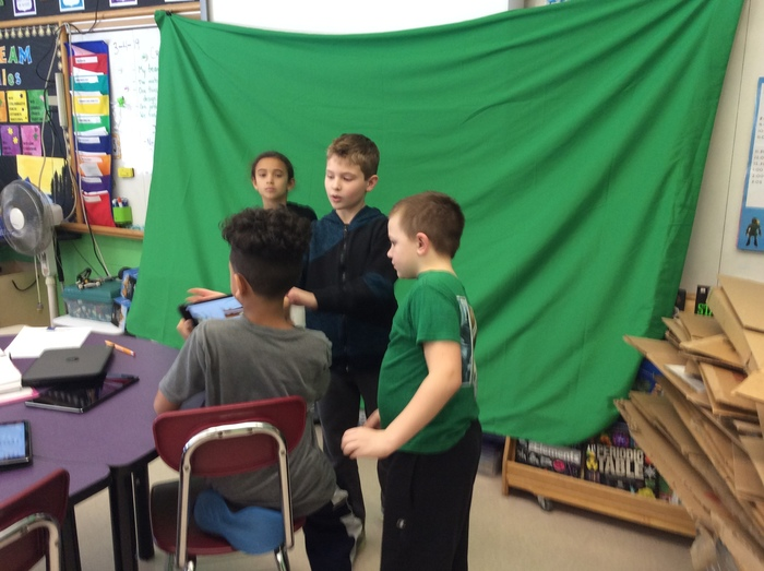 Third graders use a green screen to create a weather report.