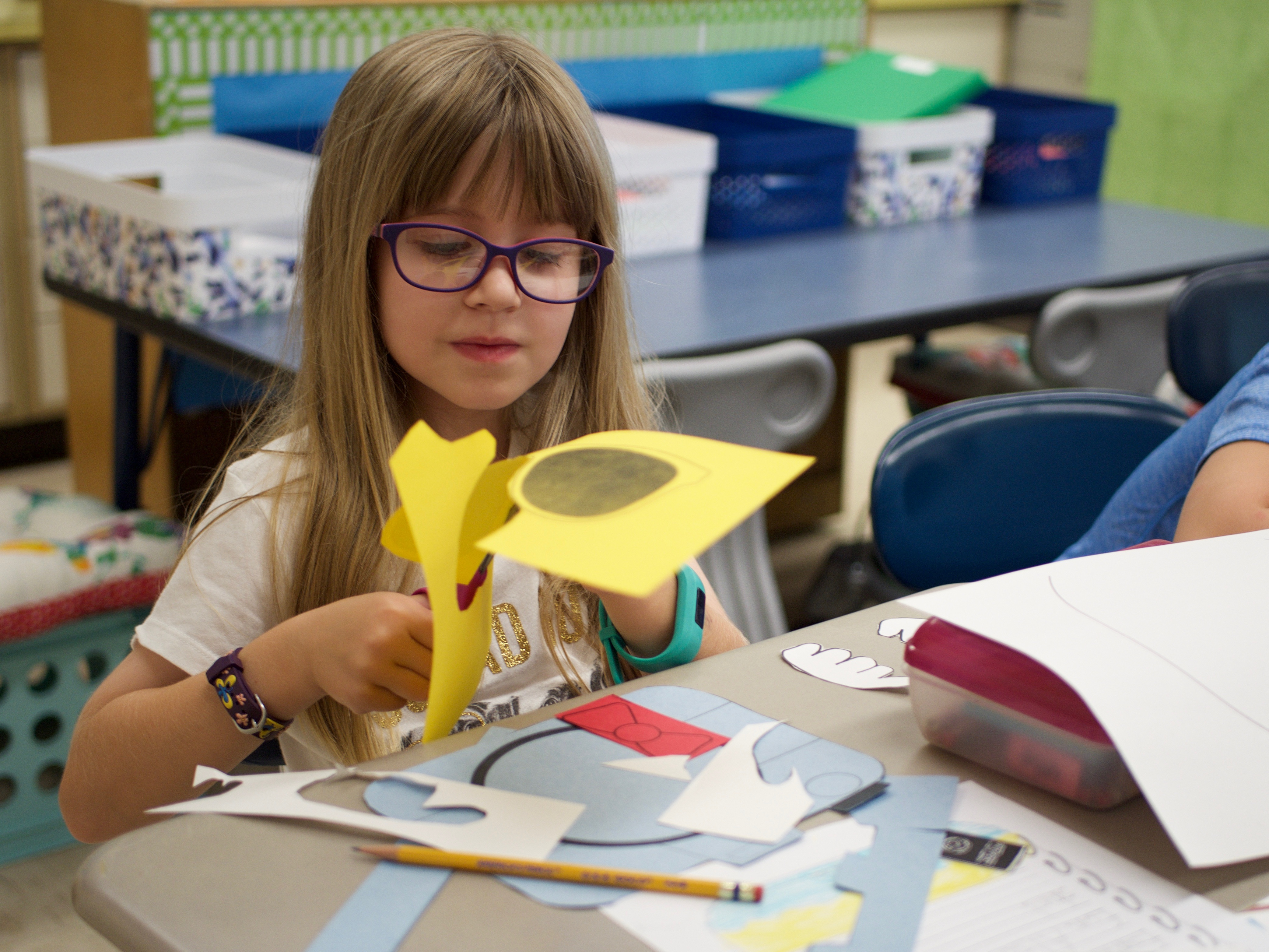 Slideshow: Girl cuts out yellow paper sunglasses with scissors
