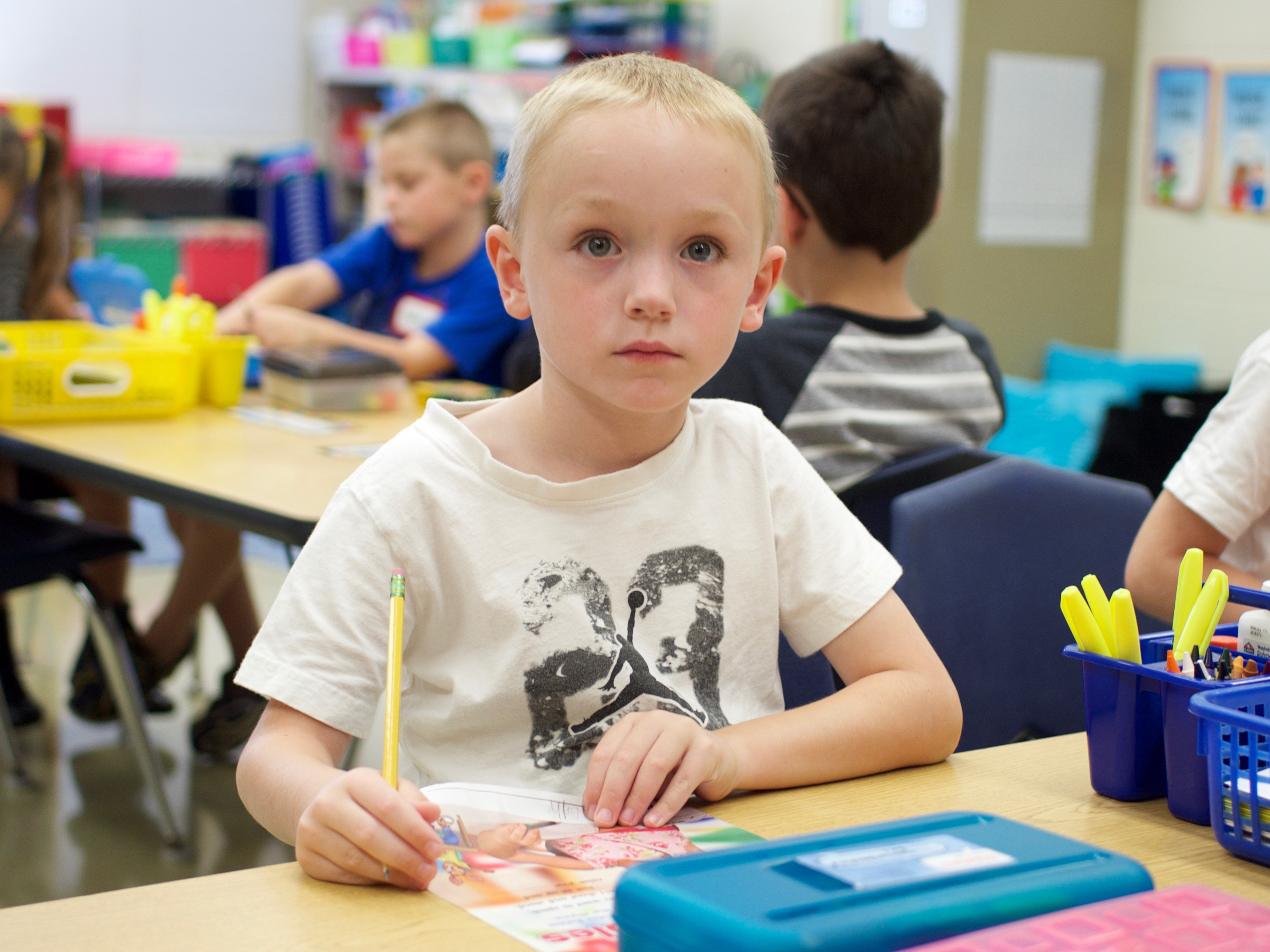 Slideshow: Boy looks at camera from desk while holding a pencil