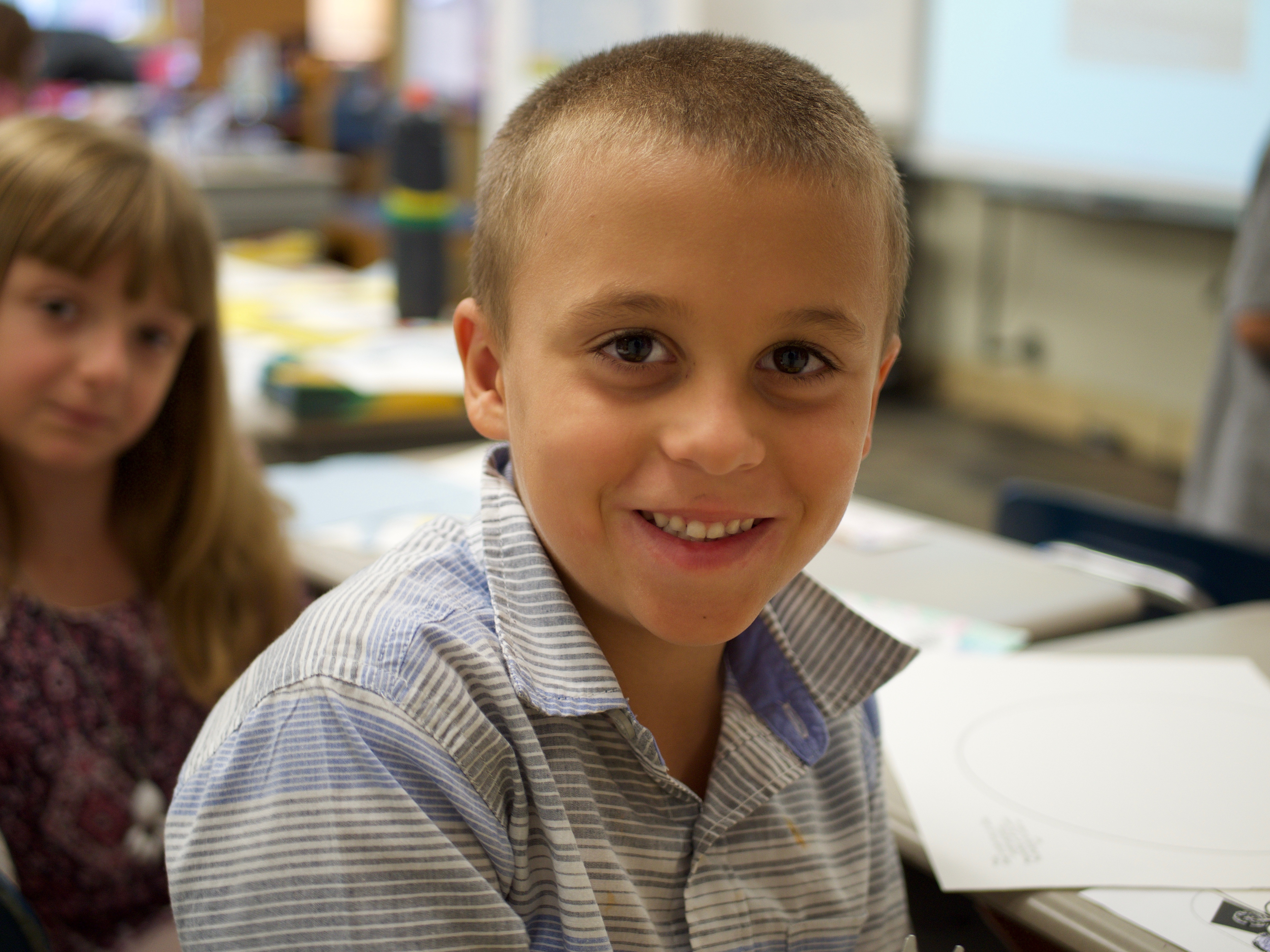 Slideshow: Boy smiles at camera from classroom desk